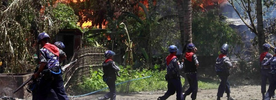 In this photo taken on June 12, 2012, Myanmar policemen walk towards burning buildings in Sittwe, capital of Rakhine state in western Myanmar. Communal violence is grinding on in western Myanmar six weeks after the government declared a state of emergency there, and Muslim Rohingyas are increasingly being hit with targeted attacks that have included killings, rape and physical abuse, Amnesty International said. A government spokesman for coastal Rakhine state, which was engulfed by a wave of bloody unrest in June, called the allegations made Friday, July 20, 2012 groundless and biased. (AP Photo/Khin Maung Win)