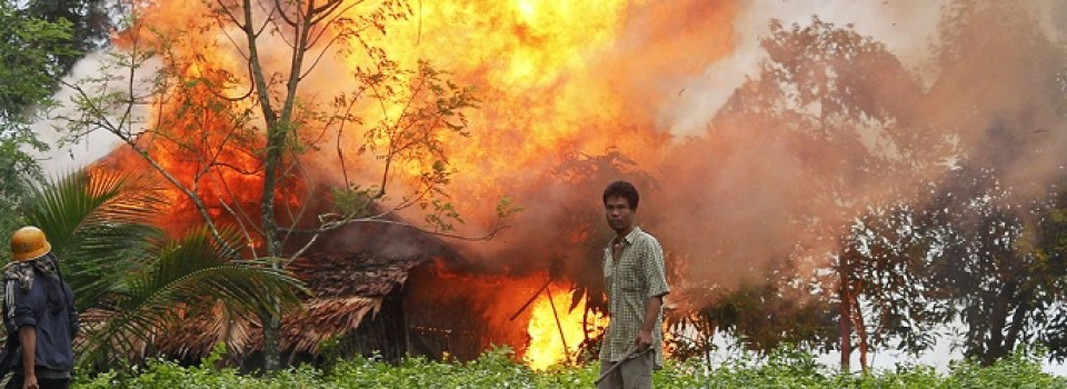 Ethnic Rakhine men hold homemade weapons as they walk in front of a house that was burnt during fighting between Buddhist Rakhine and Muslim Rohingya communities in Sittwe