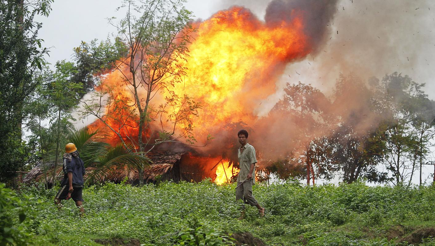 Op deze foto - gemaakt op 10 juni 2012 - loopt een Rakhine boeddhist met zelfgemaakte wapens voor een zojuist in brand gestoken huis van een Rohingya-gezin.