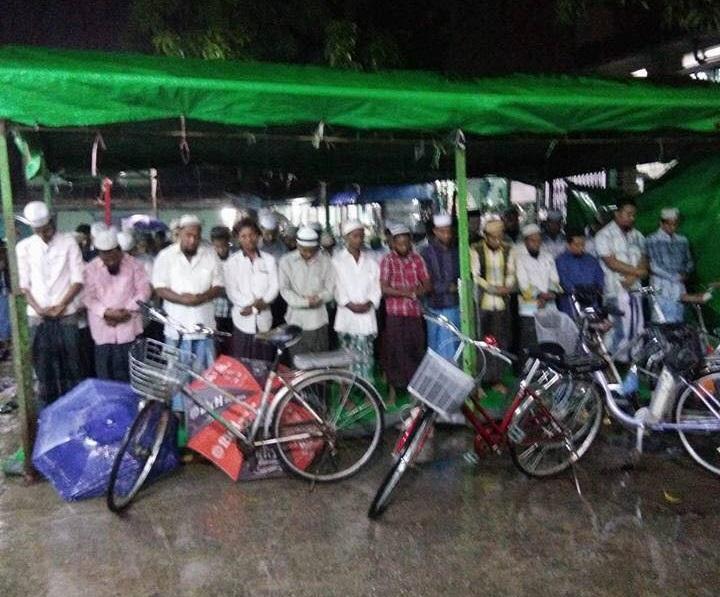 Onder plastic zeil kon een deel van de moslims relatief droog staan terwijl regen de straten van Yangon teisterde.