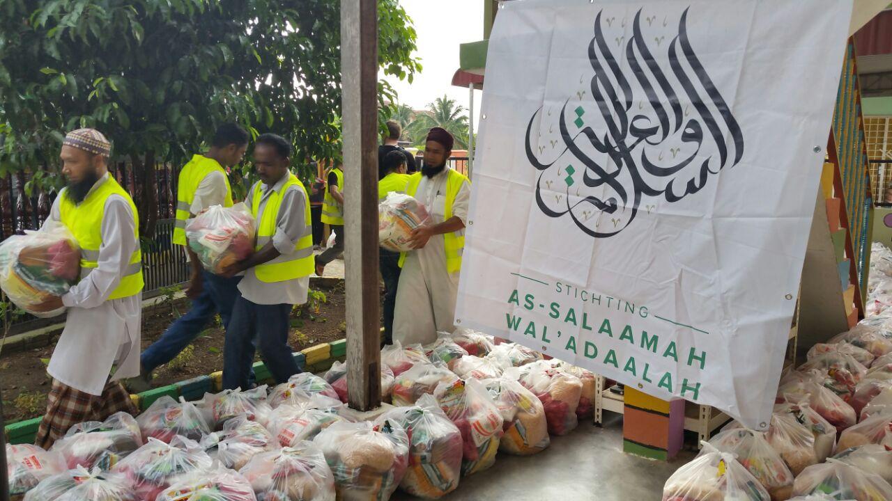 Vrijwilligers dragen de voedselpakketten naar het distributiepunt.